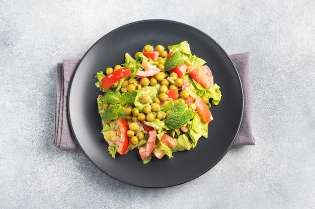 緑のトマトの葉とエンドウ豆の缶詰のサラダを黒いプレートにソースで味付けしました。春のフレッシュダイエットサラダ。上面図のコピースペース。