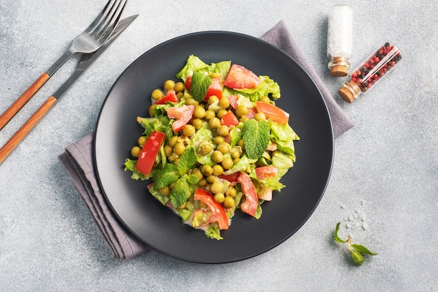 黒いプレートにソースで味付けしたグリーントマトの葉とエンドウ豆の缶詰のサラダ。春のフレッシュダイエットサラダ。上面図