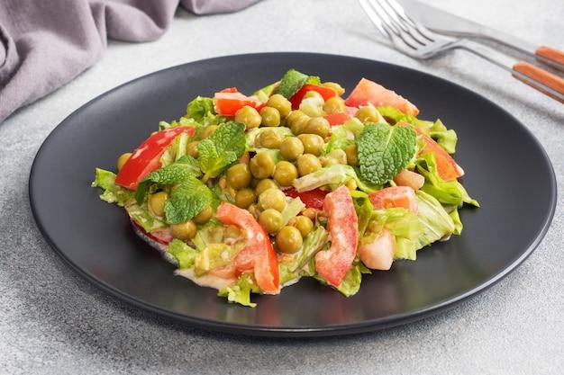 緑のトマトの葉とエンドウ豆の缶詰のサラダを黒いプレートにソースで味付けしました。春のフレッシュダイエットサラダ。