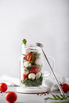 Салат из моцареллы, помидоров черри и рукколы в стеклянной кружке, на светлом фоне