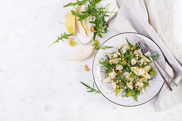 Салат из груши, голубого сыра, винограда, рукколы и орехов с пикантной заправкой на светлом фоне. здоровое питание. вид сверху, сверху