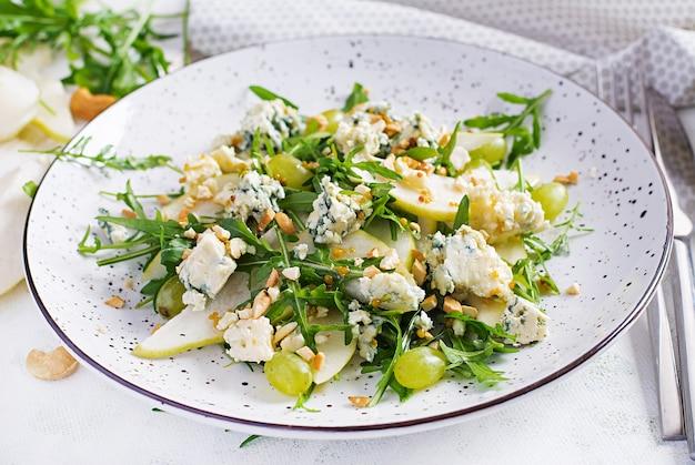 Салат из груши, голубого сыра, винограда, рукколы и орехов с пикантной заправкой на светлом фоне. здоровое питание.