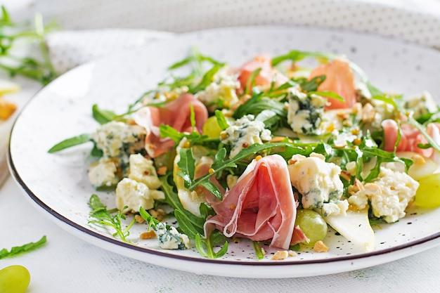 Салат из груши, голубого сыра, винограда, прошутто, рукколы и орехов с пикантной заправкой на светлом фоне. здоровое питание.