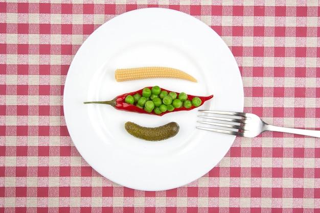 とうもろこし、えんどう豆、きゅうり、赤唐辛子の白皿に漬け込んだサラダ