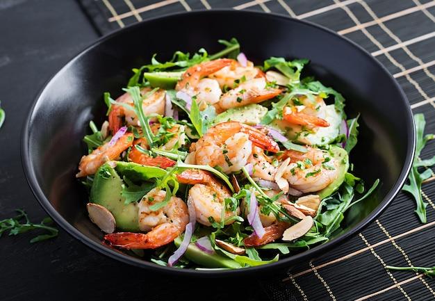 Салат из креветок. салат из креветок, рукколы, ломтика авокадо, красного лука и миндальных орехов. здоровая концепция.