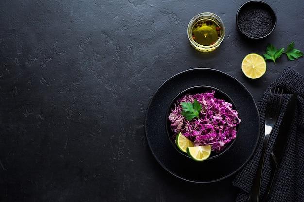 Салат из пурпурной пекинской капусты с оливковым маслом, лаймом и черным кунжутом в керамической тарелке на темной бетонной поверхности.