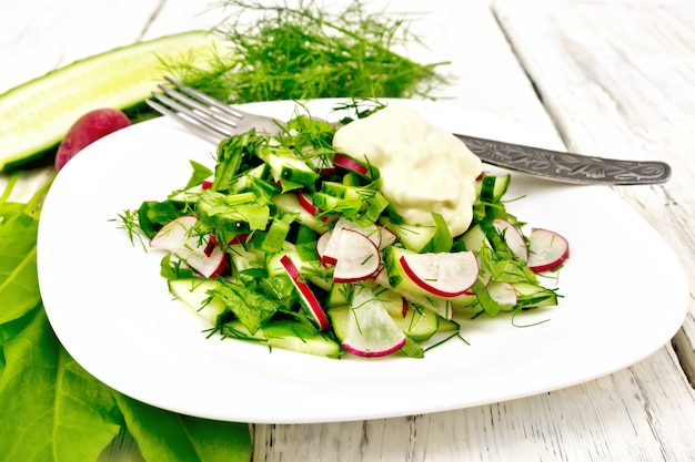 大根、きゅうり、スイバ、緑のサラダ、木の板の背景に白いプレートにマヨネーズをまとった