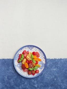 青いプレートに緑のバジルの葉と赤と黄色のチェリートマトのサラダ