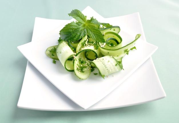 민트 잎을 곁들인 허브와 참깨를 곁들인 얇게 썬 녹색 오이 샐러드