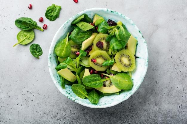 회색 콘크리트 표면에 오래 된 세라믹 접시에 시금치 아기 잎, 물냉이, 키위, 아보카도, 석류 샐러드. 선택적 초점. 평면도.