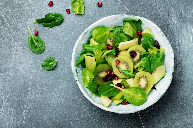 회색 콘크리트 표면에 오래된 세라믹 접시에 시금치 아기 잎, 물냉이, 키위, 아보카도, 석류 샐러드
