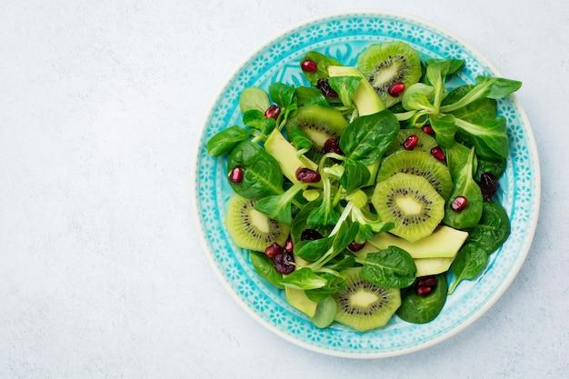 시금치 아기 잎, 물냉이, 키위, 아보카도, 석류 흰색 빛 나무 표면에 파란색 세라믹 접시에 샐러드. 선택적 초점. 평면도.