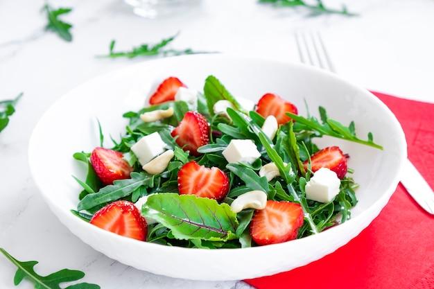 아루굴라 시금치를 곁들인 딸기 샐러드는 치즈와 견과류를 남기고 건강한 음식과 생식 다이어트
