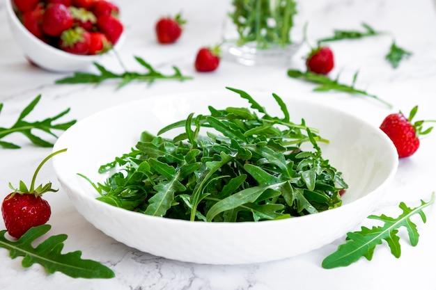 아루굴라 시금치를 곁들인 딸기 샐러드는 샐러드와 딸기 과일이 있는 대리석 테이블에 나뭇잎