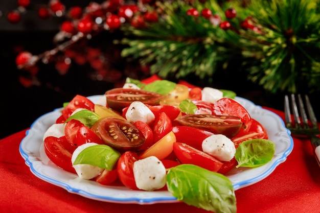 Салат из помидоров, сыра моцарелла и базилика. вегетарианское блюдо на новый год или рождество.