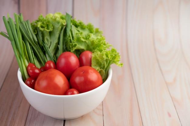 木の床に白いカップにトマトとネギのサラダ。