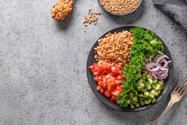 신선한 여름 야채, 토마토, 오이, 녹색 텍스트위한 공간이있는 회색 테이블에 철자가 전체 곡물 시리얼 샐러드. 위에서 봅니다.