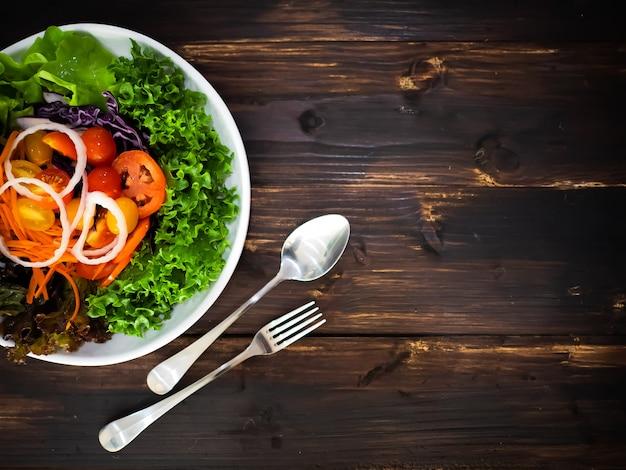 하얀 접시에 유기농 샐러드 포함 토마토, 양상추, 양파, 건강 한 다이어트를 위해 나무 테이블에 은색 포크와 숟가락 당근 프리미엄 사진