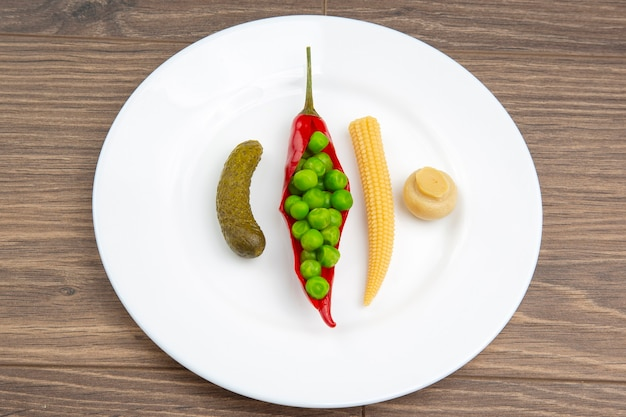 Salad of pickled and pickled corn, peas, cucumber and red pepper on a white plate.