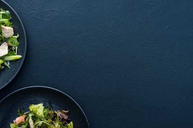 Тарелка салата на синем фоне. вегетарианская еда. полноценное органическое питание