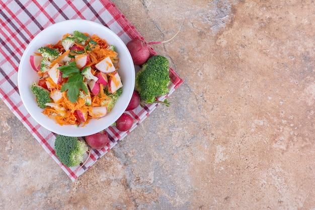 Салатное блюдо из различных овощей на полотенце на мраморной поверхности