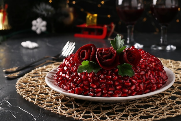 暗い背景のサラダザクロブレスレット。伝統的なロシアの新年のお祝いサラダ