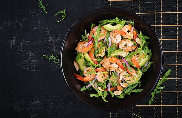 Salad of prawns. salad of shrimps, arugula, avocado slice, red onion and almond nuts. healthy concept. top view, overhead