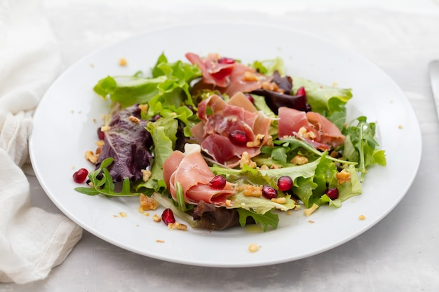 Salad prosciutto with pomegranate on white plate