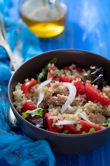 Салат из киноа с тунцом, помидорами и салатом в коричневой миске на синем деревянном фоне