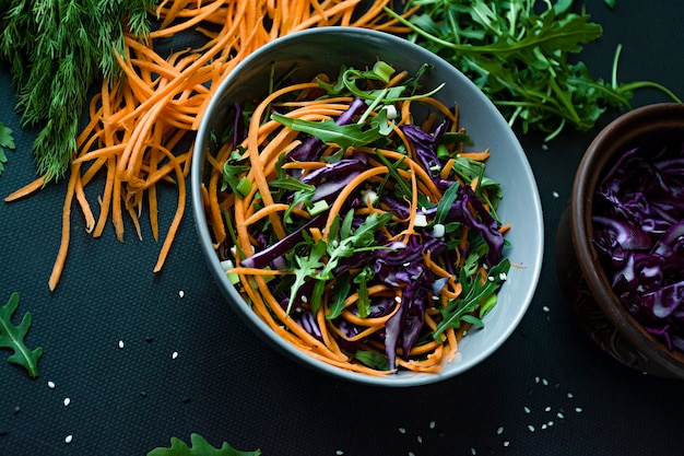 Salad of red cabbage, carrots and greens. decorated with sliced vegetables and herbs.