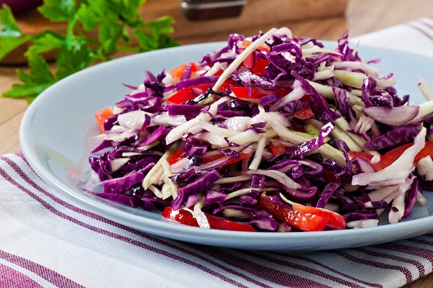 Salad of red and white cabbage and sweet red pepper, seasoned with lemon juice and olive oil in wooden bowl