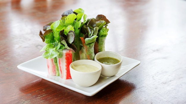 Salad roll and salad dressing on a white plate.