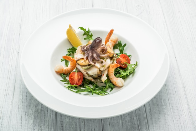 Salad of seafood and vegetables with arugula and tomatoes