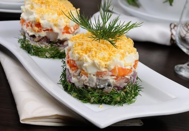 샐러드에 다진 청어와 감자 당근 양파 마요네즈를 뿌린 계란