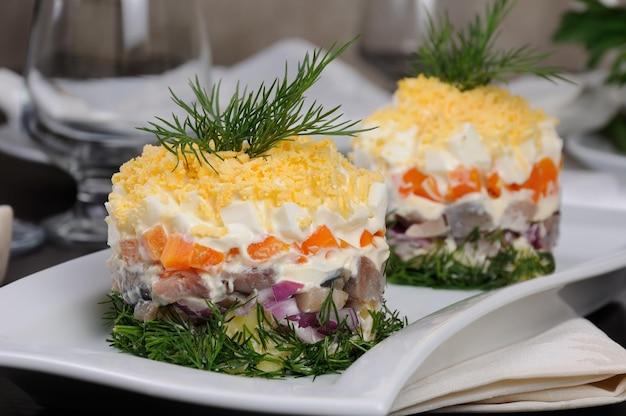 샐러드 겹겹이 청어와 감자 당근 양파 강판 계란 노른자를 뿌린 계란 마요네즈