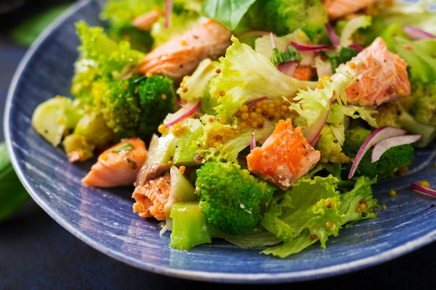 Salad of stewed fish salmon, broccoli, lettuce and dressing. fish menu. dietary menu. seafood - salmon.