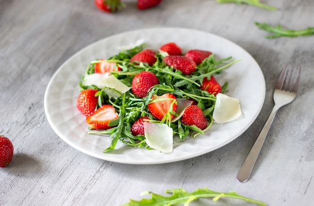 Salad of strawberries, arugula and cheese on a grey background. dietary food.