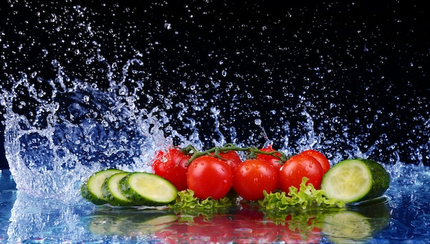 Salad, tomato and cucumber with water drop splash