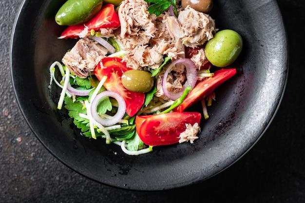 Салат из тунца свежие морепродукты овощи помидоры оливковые консервы из тунца тарелка на столе здоровая еда