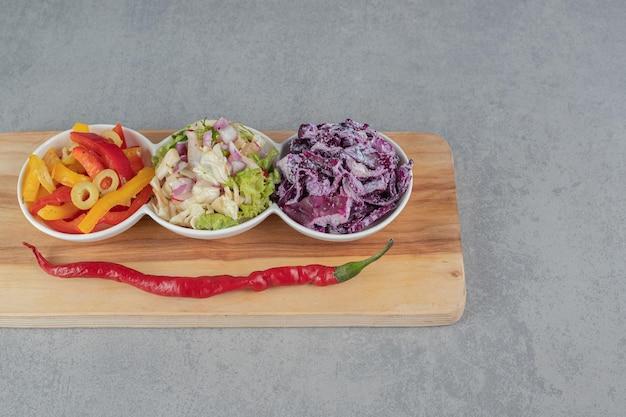 Сорта салата в чашках на деревянном блюде.