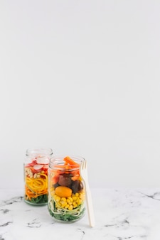 Salad vegetables in two mason jar with fork against white background