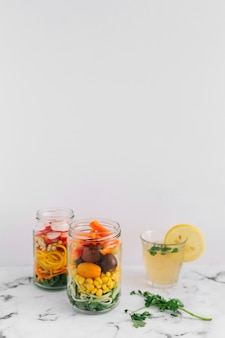 Salad vegetables in two mason jar with glass of lemon juice on marble top