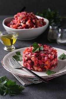 어두운 회색 표면에 비트, 감자, 당근, 콩, 피클, 양파 및 식물성 기름의 샐러드 비네 그레트