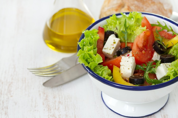 Salad in white bowl and oil