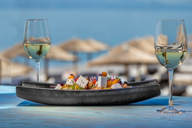 Salad with 2 glasses of wine next to the sea
