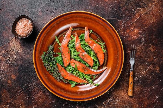 Салат с рукколой и кусочками копченого филе лосося. темный фон. вид сверху.
