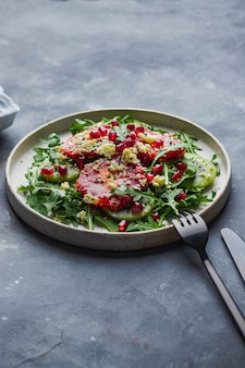 ルッコラ、キウイ、ブラッドオレンジ、ごま、キャラウェイ、ガーネット、ドルブルーのサラダ、黒いフォークとナイフで青い石の壁に焼き。健康的な食事のコンセプトです。 copyspaceの上面図