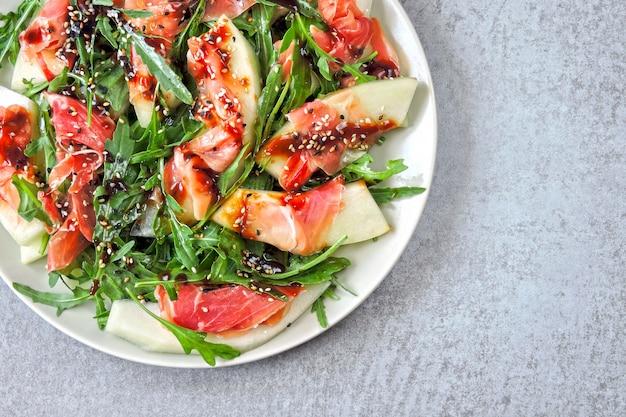 Салат с рукколой, дыней и прошутто. кето диета. палео диета. пеганская диета. концепция красивой и вкусной диетической пищи.