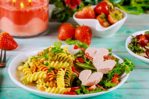 Salad with arugula, rotini pasta with hot dogs and strawberries