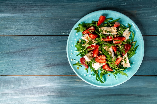 Salad with arugula, strawberries and cheese brie, camembert. long banner format. space for text. top view